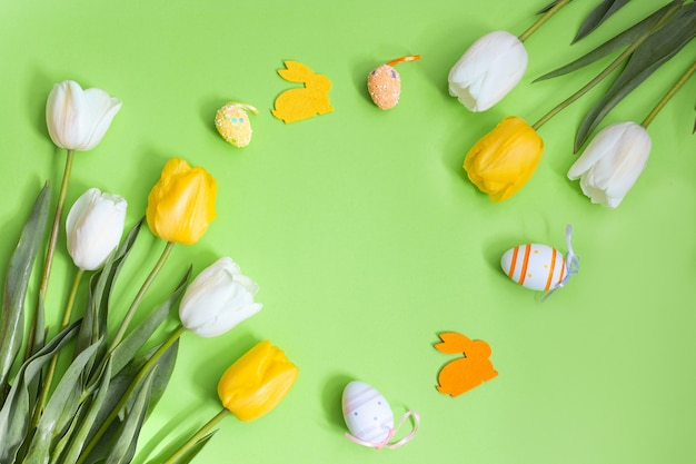 Color easter eggs and bunny with white, yellow tulips on a green background. Premium Photo