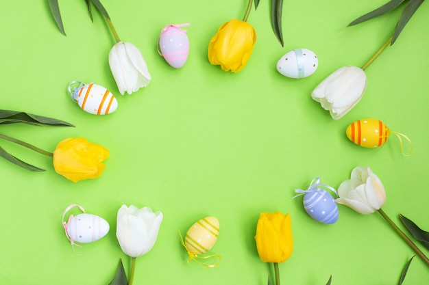 Color easter eggs and white yellow tulips on a green background. Premium Photo