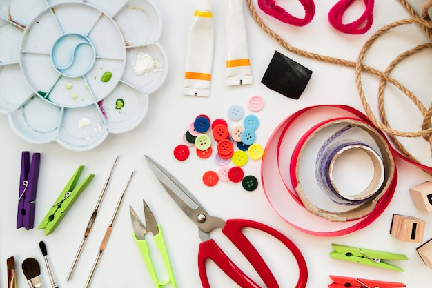 Color palette; acrylic paint tube; crochet needles; buttons; ribbon; scissor; clothespin and string isolated on white background Free Photo