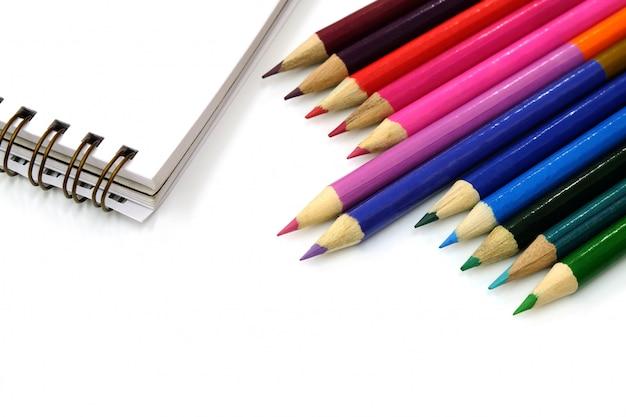 色鉛筆と白い背景の上のノート Premium写真