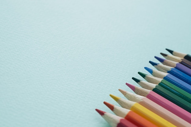 Color pencils on a blue background. pencils for drawing. Premium Photo