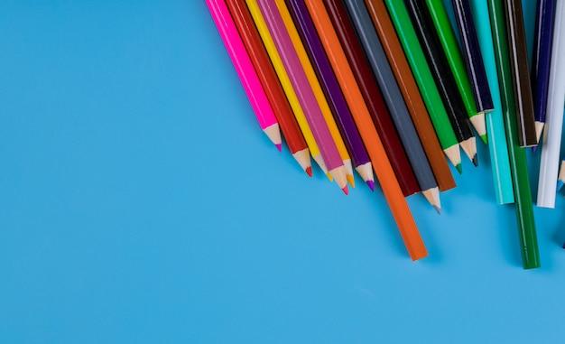 Color pencils on blue background, school supplies Premium Photo