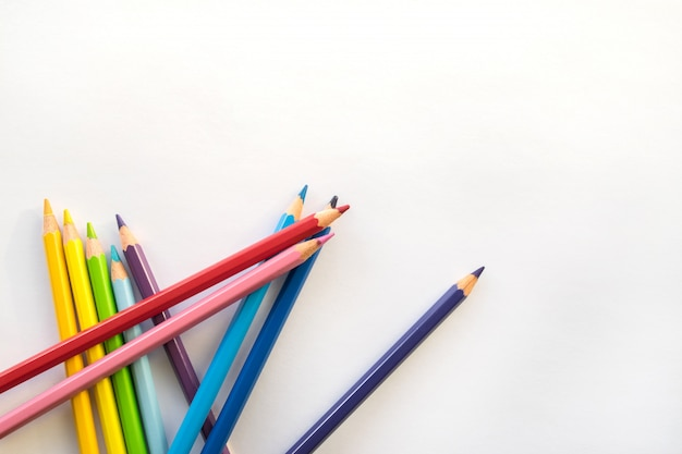 Color pencils on white paper background, copy space. office supplies, back to school. Premium Photo
