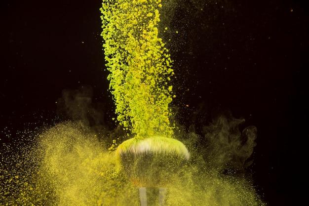 Color powder cascade falling on foundation brush Free Photo