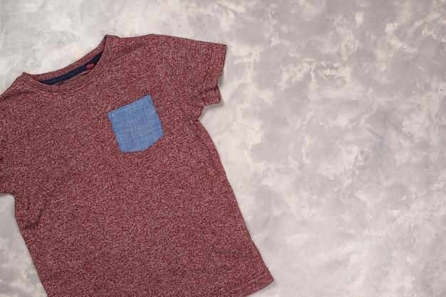 カラーtシャツのモックアップ、上面図。コンクリートの灰色の背景にtシャツ、コピースペース。 Premium写真