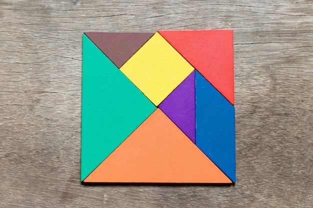 Color tangram in square shape on wood background Premium Photo