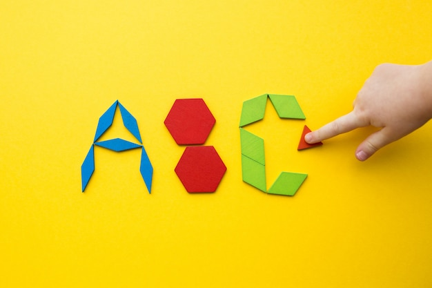 Color wood tangram puzzle in alphabet abc letters shape on yellow background with the hand of a child Premium Photo