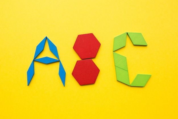 Color wood tangram puzzle in alphabet abc letters shape on yellow background Premium Photo