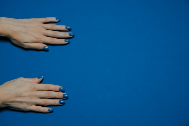 Color of the year 2020. beautiful manicured woman's nails with classic blue nail polish Premium Photo