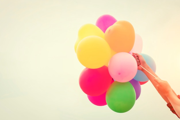 Colored balloons held by arms Free Photo