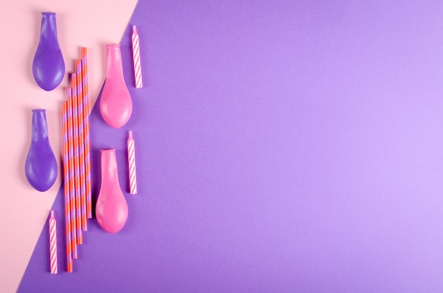 Colored candles and air balloons composition on purple background, party and celebration decoration. Premium Photo