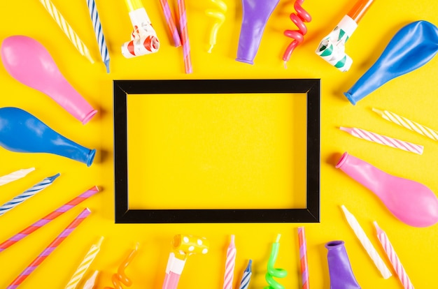 Colored candles and air balloons composition on yellow background, party and celebration decoration. Premium Photo