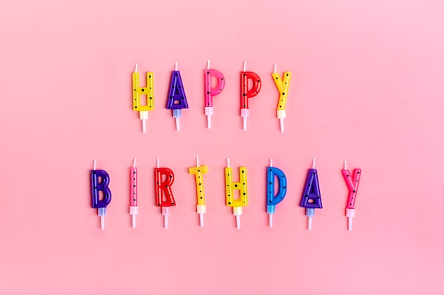 Colored candles on cake in form of letters happy birthday on pink Premium Photo