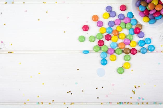 Цветные конфеты, разбросанные по поверхности белой деревянной доски studio photo Premium Фотографии