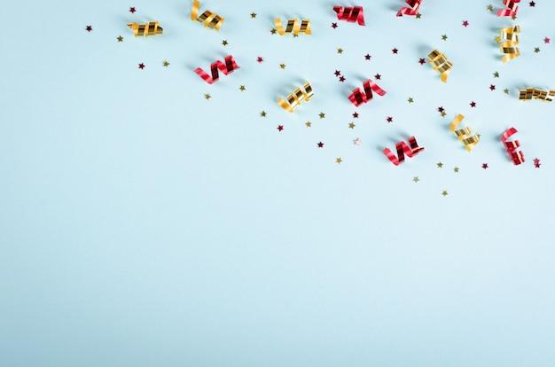Colored confetti composition on blue background, party and celebration decoration. Premium Photo