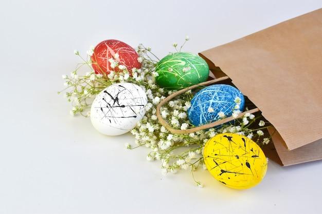 紙袋に入った色付きの卵。イースターの配達。 Premium写真
