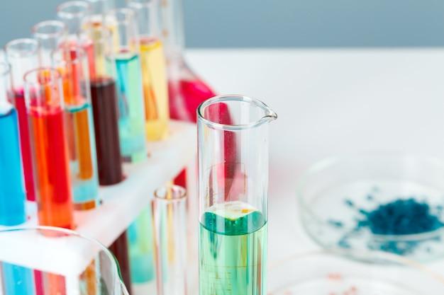 Colored liquids inside lab glassware on white table in laboratory Premium Photo