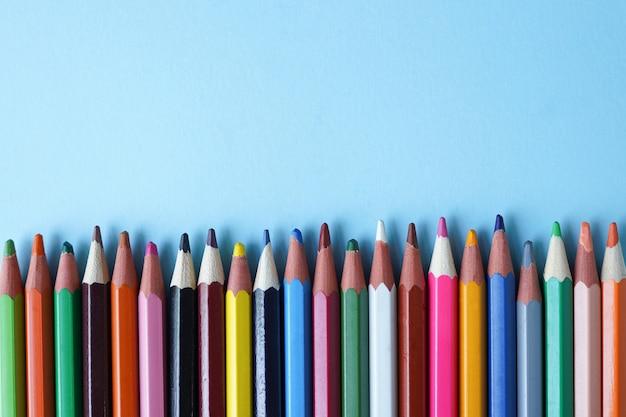 Colored pencils on blue, copy space. Premium Photo