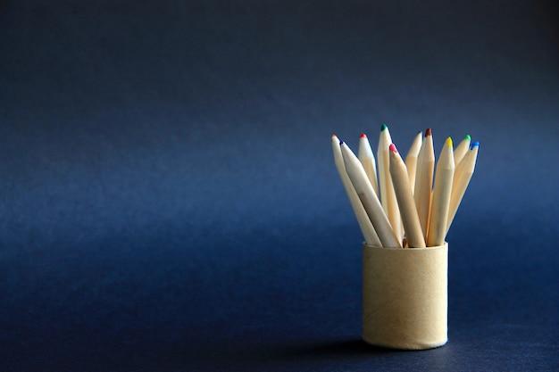 Colored pencils in a cardboard box on a dark background Premium Photo