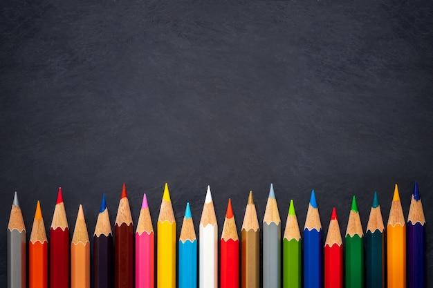 Colored pencils on chalkboard background Premium Photo