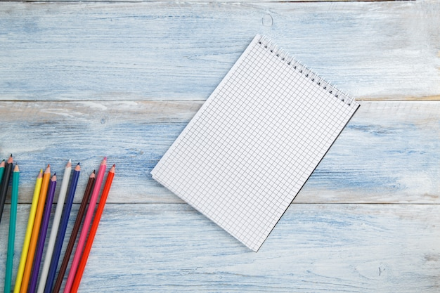 Colored pencils or crayons and notepad on a blue and white scuffed vintage wood, top view Premium Photo