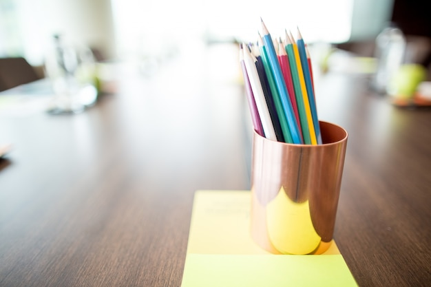 Colored pencils in cup on conference table Free Photo