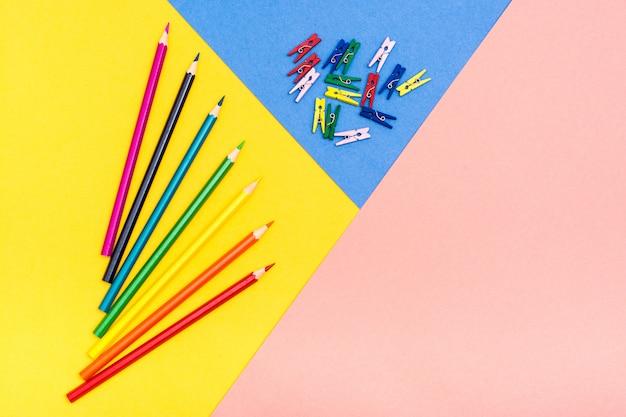 Colored pencils lie like a fan on a tricolor background Premium Photo