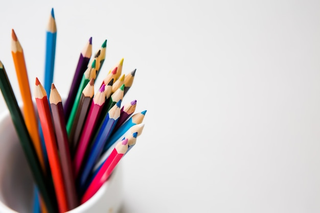 Colored pencils on white background with copyspace Premium Photo