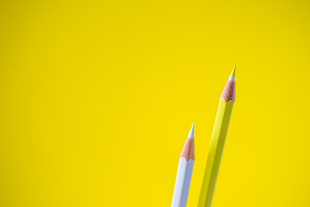 Colored pencils on a yellow background with space for text. Premium Photo