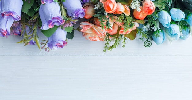 Colored roses with branches on white wooden background, flat lay. Free Photo