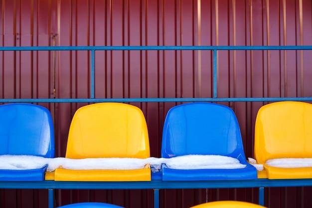 Colored seats snow covered in winter snowy stadium. snow covered tribune Premium Photo