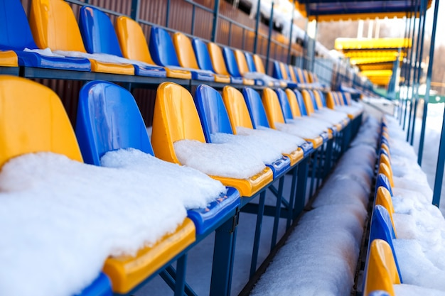 Colored seats snow covered in winter snowy stadium. Premium Photo