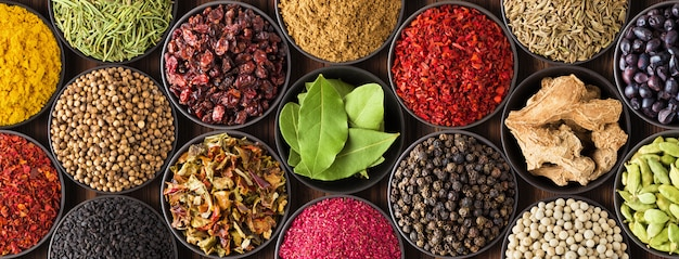 Colored spice background, top view. collection indian seasoning in cups Premium Photo