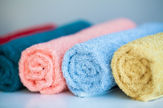 Colored towels on white table with copy space on bath room background. Premium Photo