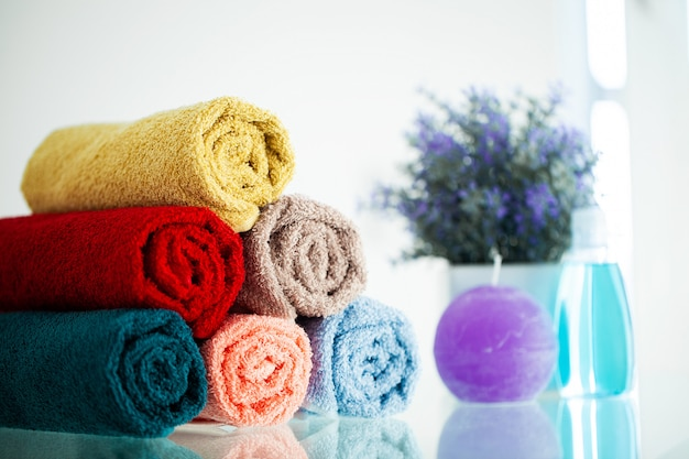 Colored towels on white table with copy space on bath room Premium Photo