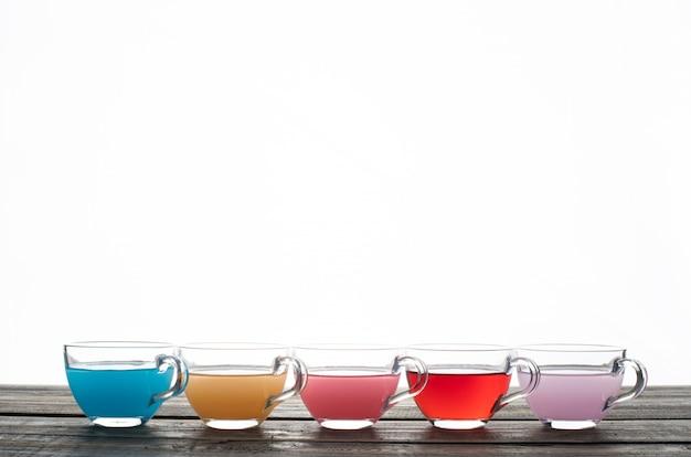 白い背景の上のカップの色の水。側面図。テキストのためのスペース 無料写真