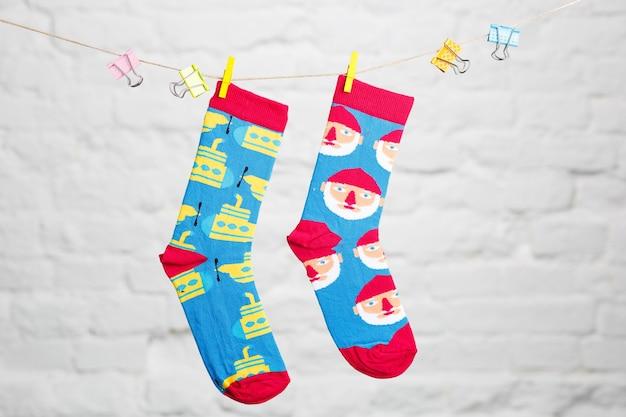 Цветные зимние повседневные носки, висящие на нитке и перевязанные тканью на фоне белого кирпича. Premium Фотографии
