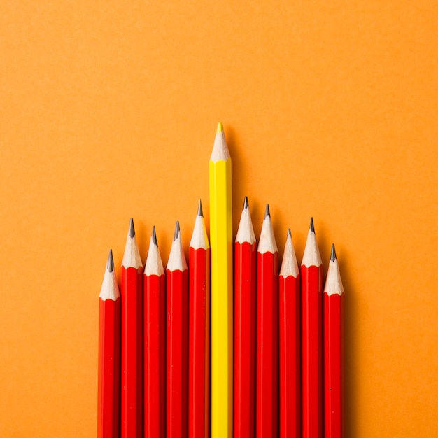 Colored yellow pencil between the red pencils on an orange background Free Photo