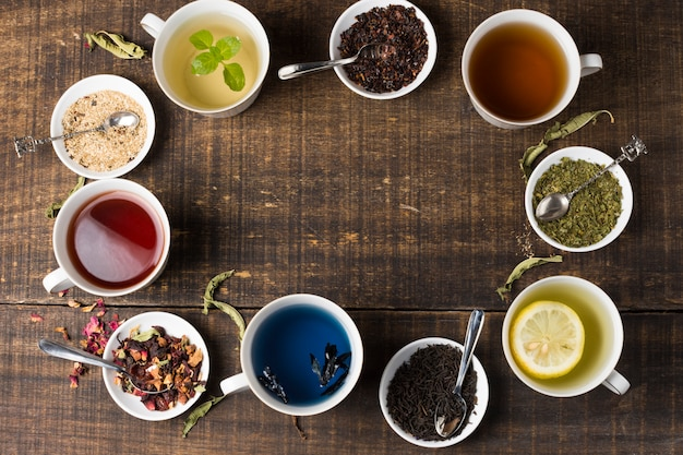 Colorful aroma tea cups arranged in circular position on wooden desk Free Photo