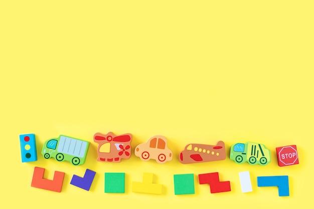 黄色の背景にカラフルな赤ちゃん子供の木のおもちゃ。カラフルなブロック、車、飛行機の開発。上面図。フラット横たわっていた。テキストのスペースをコピー Premium写真