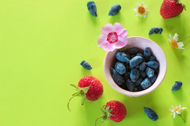 夏の果実と緑の紙の上に花のカラフルな背景。 Premium写真
