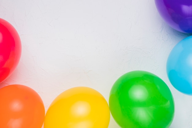 Colorful balloons arranged on white surface Free Photo