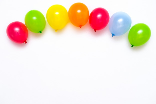 Colorful balloons on white wall or table top view. festive or party background. flat lay style. copyspace for text. birthday greeting card. Premium Photo