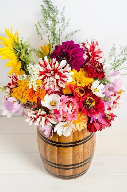 白い表面の上に花瓶に庭の花のカラフルな美しい花の花束。 Premium写真