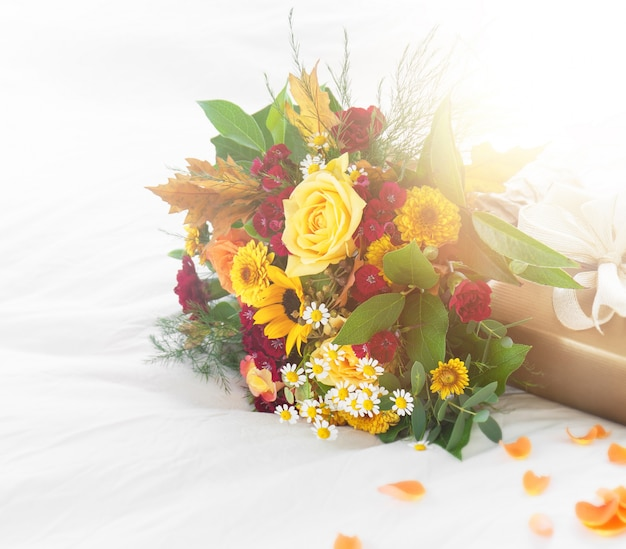 Colorful beautiful spring or summer bouquet of flowers on bed with golden gift box, holiday or surprise concept Free Photo