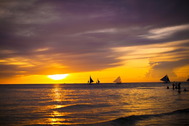 Colorful beautiful sunset with sailboat on the horizon in boracay island Premium Photo
