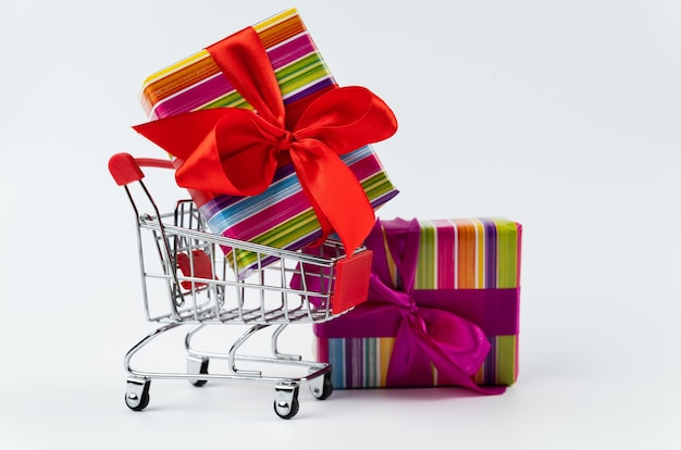 Colorful black friday gift in shopping cart Free Photo
