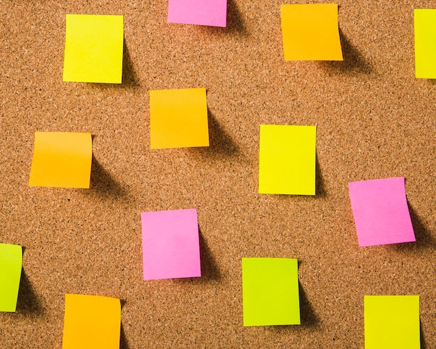Colorful blank sticky notes on cork board Free Photo