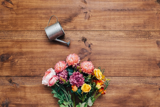 Colorful bouquet with watering can Free Photo