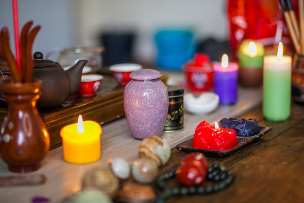 Colorful burning candles; ceramic vase and therapies chinese balls over wooden table Free Photo